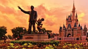 A statue of Walt Disney and Mickey Mouse holding hands, with Walt Disney pointing up to the sky
