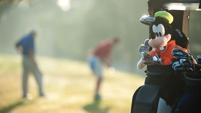 Morning golfers tee up at a resort golf course as a plush Goofy toy smiles from their golf bags