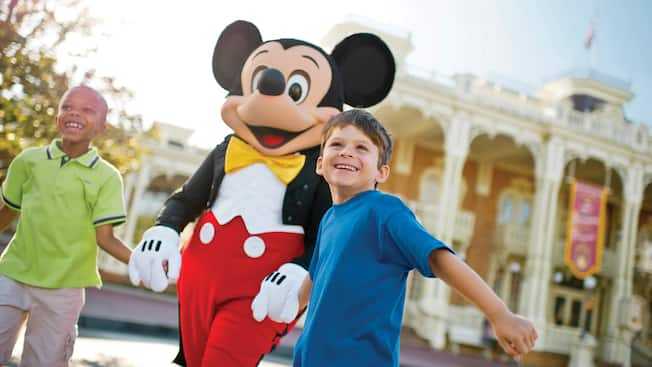 Two excited young boys hold Mickey's hand as they walk down Main Street at Walt Disney World Resort