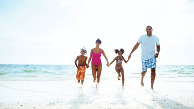 Family on the beach runs through the ocean surf holding hands and laughing