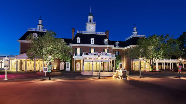 A complex of Victorian style buildings, with a sign that says The American Adventure, at night