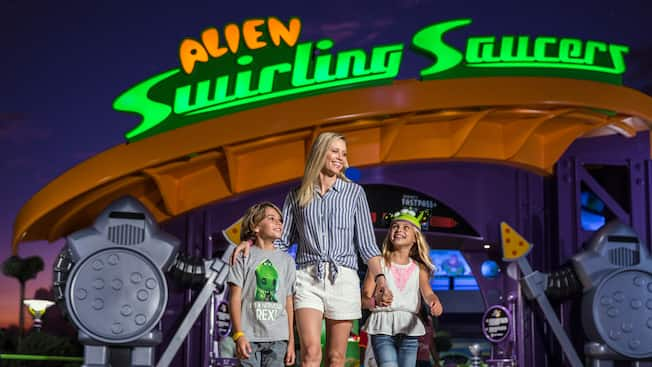 A woman and 2 kids stand in front of Alien Swirling Saucers