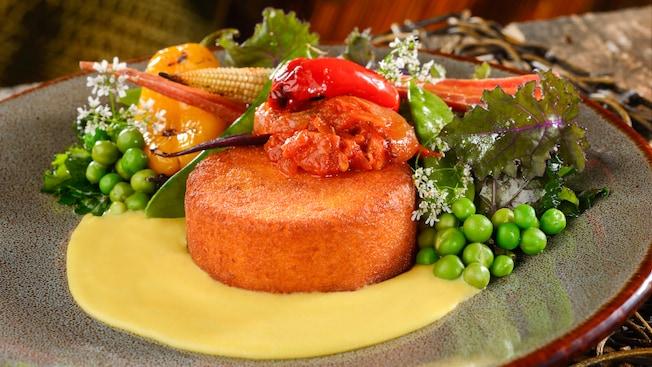 Um bolo de milho acompanhando ervilhas, alface, milho, cenoura, pimentão, creme e molho de tomate