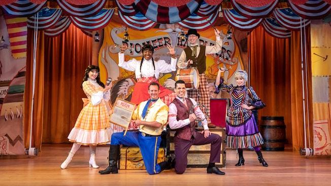 3hombres y 3mujeres del elenco de Hoop-Dee-Doo Musical Revue posan en el escenario con instrumentos musicales.