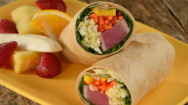 Two halves of a spicy tuna wrap sit on a rectangular plate with sliced bananas, strawberries, pineapple and orange