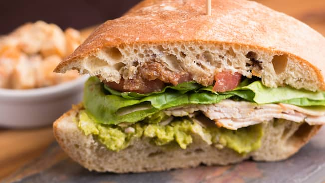 A turkey breast club hero, consisting of bacon, turkey, lettuce, tomato and avocado on a French roll