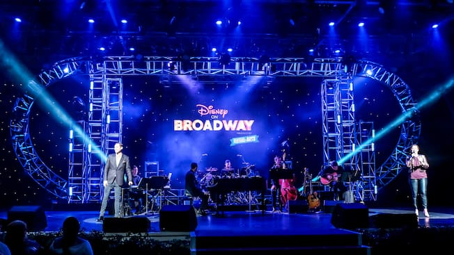 The Disney on Broadway sign lights up a stage filled with instruments at the Festival of the Arts