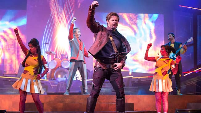Star-Lord from Guardians of the Galaxy raises his fist as he sings in front of a band