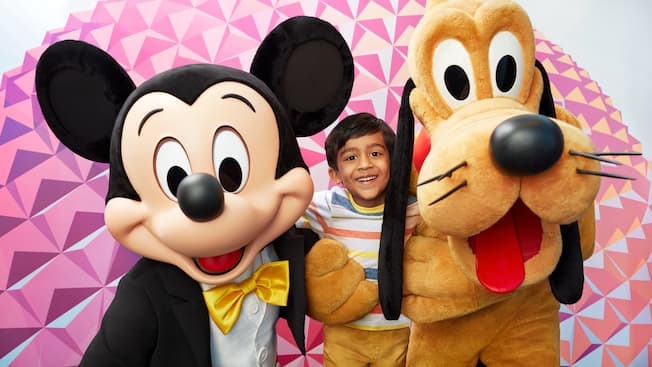 Mickey and Pluto pose for a picture with a little boy in front of Spaceship Earth