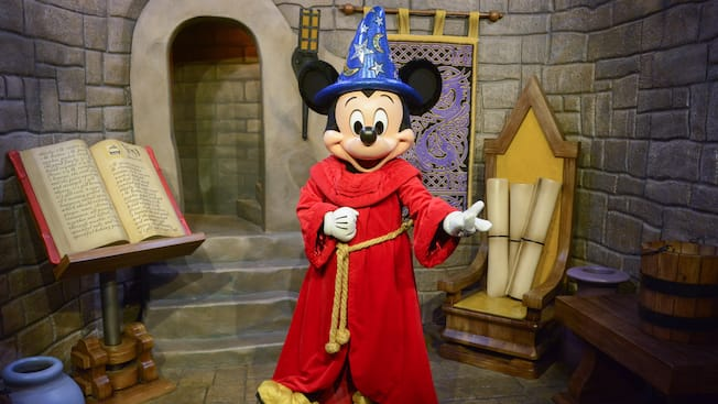 Sorccer Mickey standing next to a book of magic