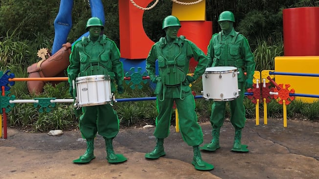 The Green Army Man Drum Corps stand, ready to play, in front of Woody and the Toy Story Land sign