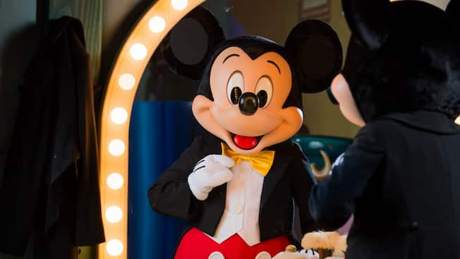 Mickey Mouse wears a tuxedo, looks into a mirror and adjusts his bow tie