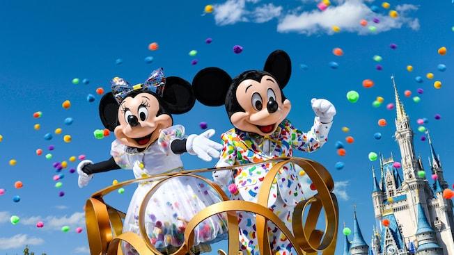 Muito confete voando ao redor do Mickey Mouse e da Minnie trajando roupas de festa com estampas de confete