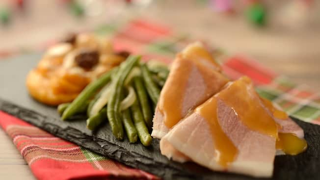 Glazed ham served with string beans and sweet potatoes