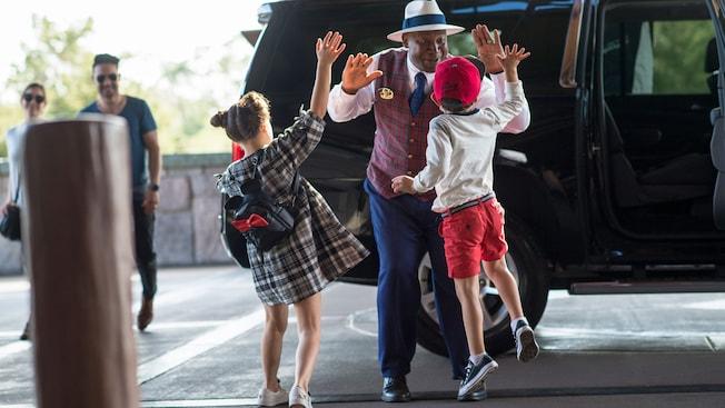 2 niños chocan los cinco con un guía turístico junto a un auto, mientras sus padres observan