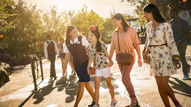 Un guía de Disney acompaña a un joven y a 2 adultos Visitantes por el Parque Temático Magic Kingdom
