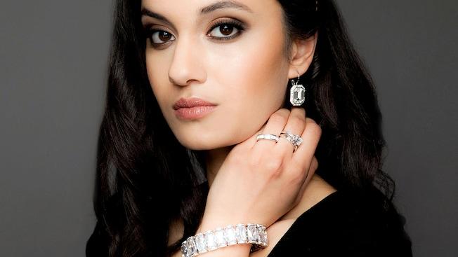 Uma mulher posando com joias inspiradas em celebridades, incluindo uma pulseira, anéis e brincos, no quiosque Filthy Rich