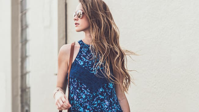 The profile of a woman modeling a floral top and accessories from francesca's boutique