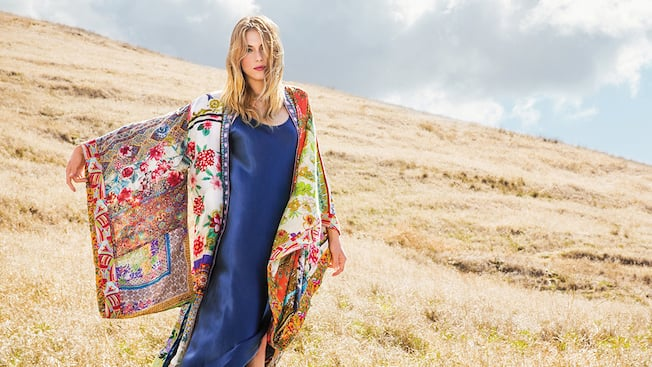 A woman in a meadow models a silk dress and patterned kimono wrap from the Johnny Was boutique