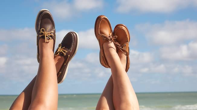Two pairs of crossed legs are in the air, featuring their calves and the boat shoes on their feet