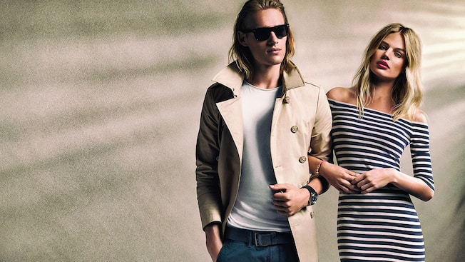 A man modeling a trench style jacket and sunglasses alongside a woman modeling an off the shoulder long sleeve dress from Superdry