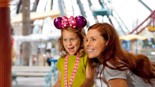 A mother and daughter playing boardwalk games at Pixar Pier in Disney California Adventure Park