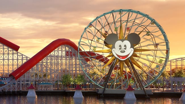 Pixar Pal A Round, a large Ferris wheel with Mickey Mouse's face at the center, standing in front of the Incredicoaster roller coaster on Pixar Pier