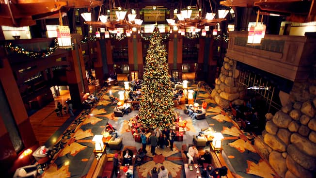 A very tall, decorated Christmas tree in the lobby of a Victorian style hotel