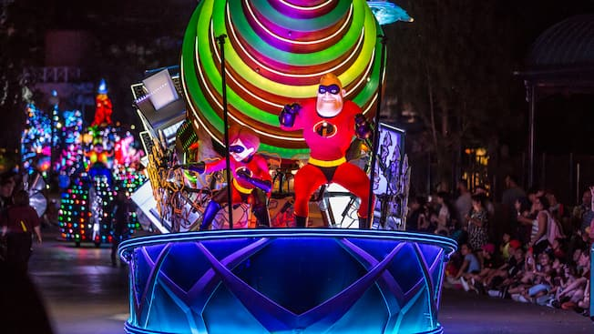 Mr. Incredible and Elastigirl wave from a parade float designed to look like a giant drill bit