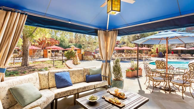 A well furnished cabana with all its curtains drawn, revealing a pool view