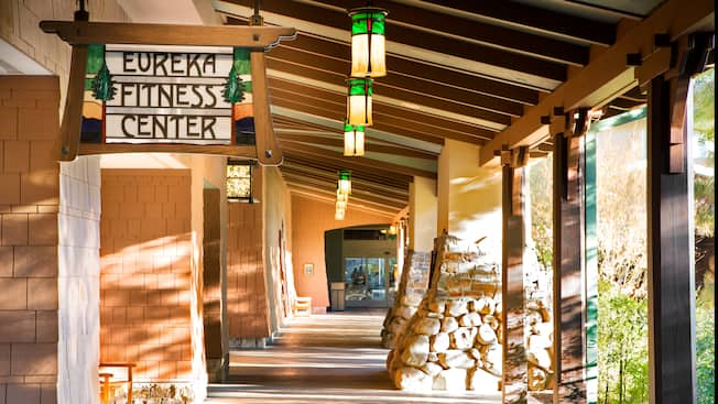 A rustic sign in an outdoor hallway identifies the entrance to Eureka Fitness Center