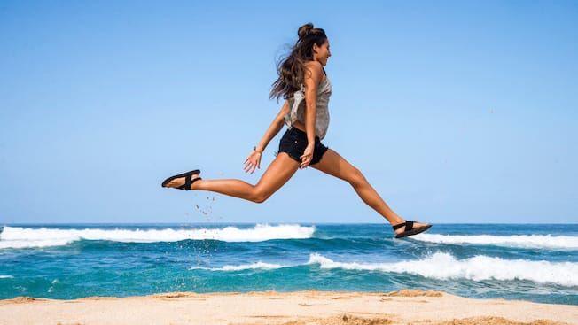 A woman wearing sandals and athletic wear runs on the beach