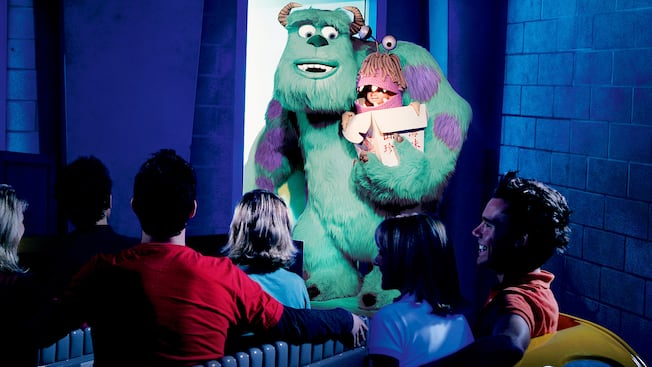 Guests ride through Monstropolis in a taxi and pass Sully holding Boo close