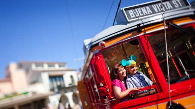 A mother and son ride the Red Car Trolley down Buena Vista Street