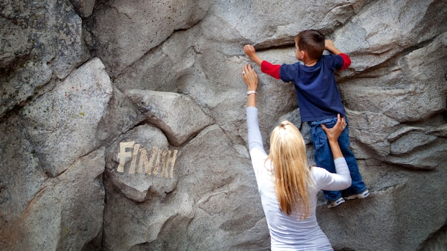 A mother helps her kid climb a rock to reach the Finish sign on the Redwood Creek Challenge Trail