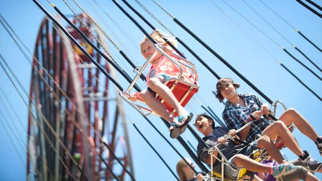 Smiling kids ride the Silly Symphony Swings at Disney California Adventure Park