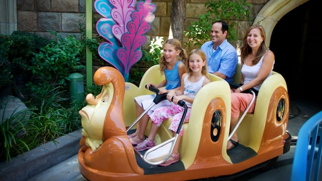 A family of 4 rides inside a giant caterpillar through the Alice in Wonderland attraction