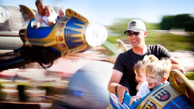 A father and his 2 young kids smile from their spinning Astro Orbitor retro rocket