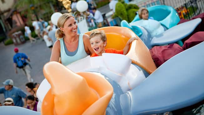 A mother and her little boy smile as they ride Dumbo the Flying Elephant
