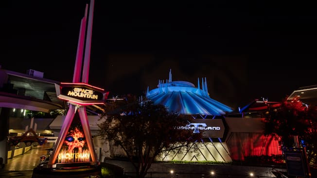 At night, a neon sign reads 'Ghost Galaxy' near ones that read 'Space Mountain' and 'Tomorrowland'