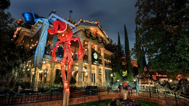 A Jack Skellington scarecrow in front of the holiday themed Haunted Mansion