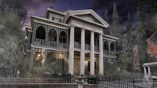 Dusk and fog settles around the eerie and ornate Haunted Mansion attraction in New Orleans Square