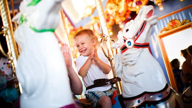 A happy boy rides a majestic horse on King Arthur Carrousel