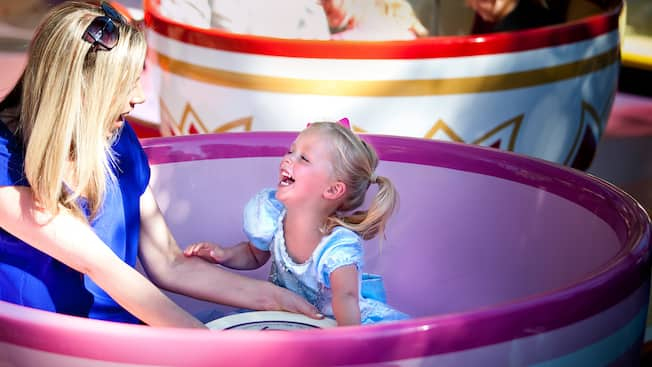 A mother and daughter giggle as they spin on the Mad Tea Party attraction