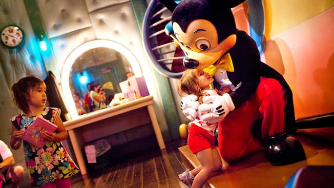 A young girl meets Mickey Mouse and gets a hug from him at his house in Disneyland Park