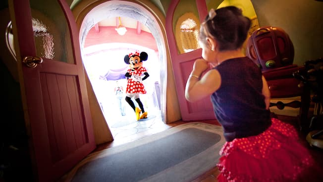 At Minnie's House, Minnie poses in the doorway while a girl, inside the house, giggles
