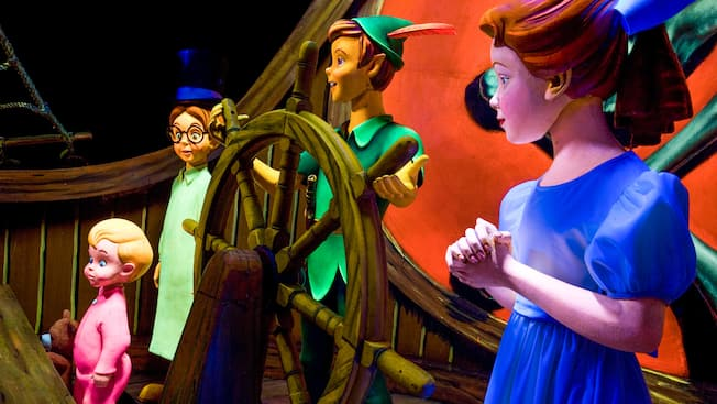 Wendy stands by Peter Pan's side as he steers a ship that takes the Darling children to Neverland