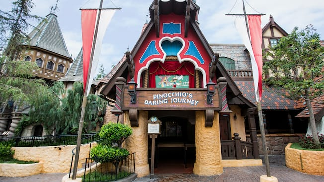 The outside of Pinocchioâ?s Daring Journey attraction at Disneyland park is styled like a storybook house with 2 stone columns on either side of an entranceway and an ornately carved balcony above it that resembles a marionette stage where a figure of Pinocchio is posed