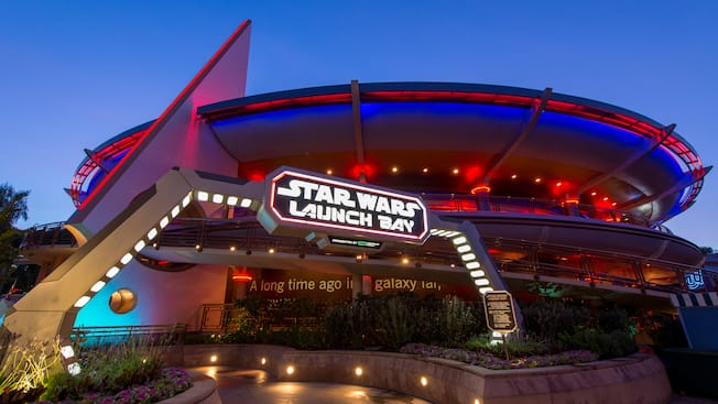 The illuminated space ship inspired entrance to the Star Wars Launch Bay as night falls