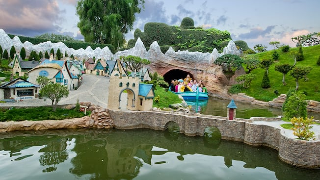 A Storybook Land Canal Boat full of Guests drifts gently past miniature villages